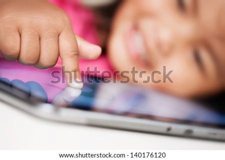 A happy kid selecting or pointing at something on a touchscreen tablet. - stock photo