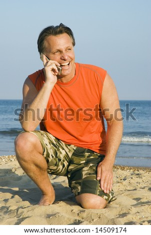 A happy laughing forties man is enjoying himself on a beautiful beach while having a conversation on his mobile phone.