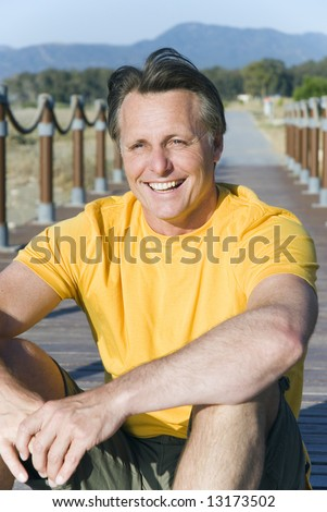 A happy laughing 44 year old man sitting on the boardwalk at the beach.