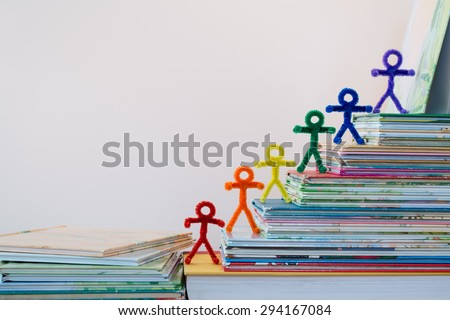 A happy line of rainbow pipe-cleaner people going up the ladder of success through reading and education. A lovely photo for international or multicultural ideas and concepts for adults and children. - stock photo