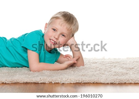 A happy little boy is resting on the white carpet - stock photo