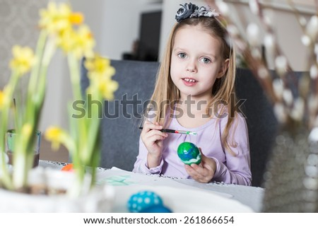 A happy little girl coloring easter eggs. Cozy home atmosphere. Easter - stock photo