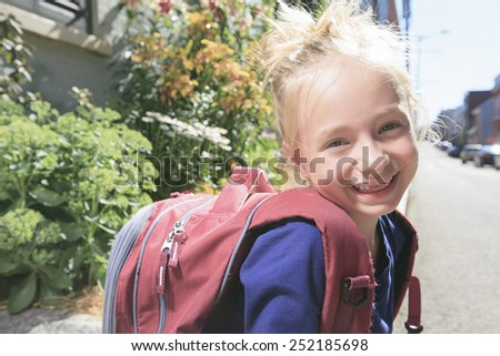 A Happy little girl outside with backpack - stock photo