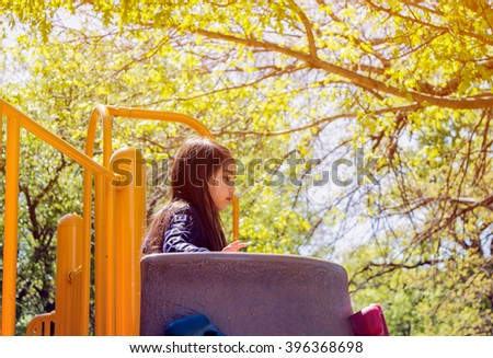 A happy little girl playing at public park with greenery background,filtered color tone in picture. - stock photo