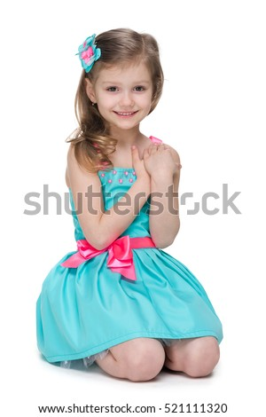 A happy little girl sits on the white background