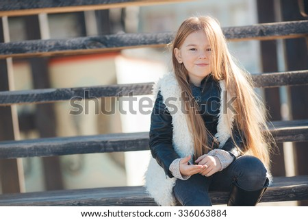 a happy little girl smiling portrait. Little girl in an urban setting smiles at the camera. autumn street portrait, kid outdoors