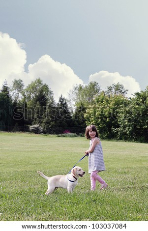 A happy little girl walks her puppy, an English Cream Labrador Retriever - Golden Retriever mixed designer breed, on a beautiful spring day. Extreme shallow depth of field.