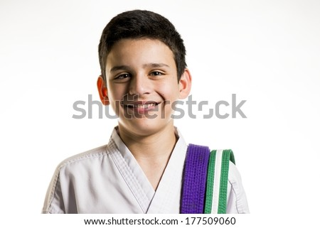 a happy looking boy in his karate uniform. - stock photo
