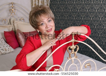 A happy loving woman sitting on bed in evening red dress