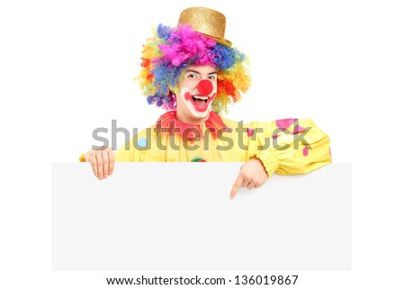A happy male clown pointing on a blank panel isolated on white background
