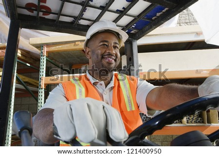 A happy  male industrial worker driving forklift at workplace - stock photo