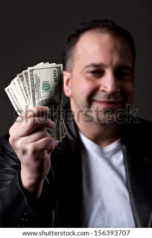 A happy man holds a handful of green American money with selective color.