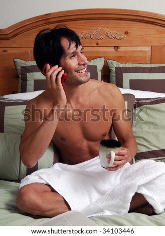 A happy man in bed talking on a cell phone and reading a paper