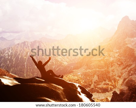 A happy man sitting on the peak of a mountain with hands raised admiring breathtaking view at sunset - stock photo