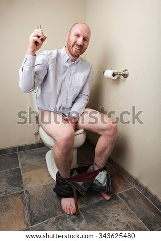 A happy man using having a phone call while on the toilet - stock photo