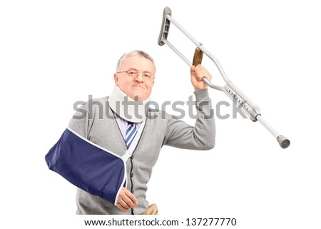 A happy mature gentleman with broken arm holding a crutch isolated on white background