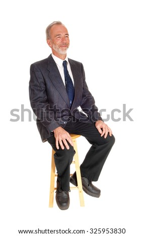A happy middle age male in a dress pants, tie and jacket sitting on a chair with a beard, isolated for white background.  - stock photo