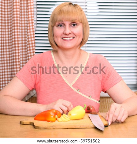 A happy middle-aged woman cooking meal - stock photo