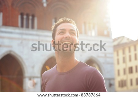 A happy moment of a boy who smiles resumed against the light - stock photo