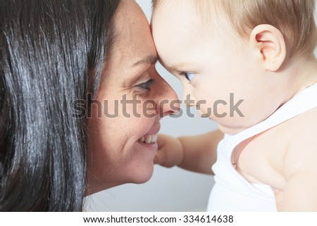 A Happy 8 month old baby boy with mother forehead to forehead.