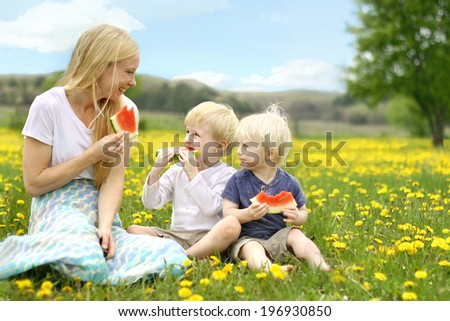 a happy mother and her two young children are sitting outside in a dandelion flower meadow, eating watermelon fruit. - stock photo