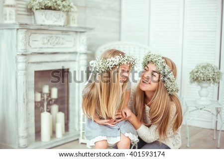 A happy mother and her young daughter are having fun. They are both laughing. They are having casual clothes and floral wreathes on. The atmosphere of happiness is all around them. - stock photo
