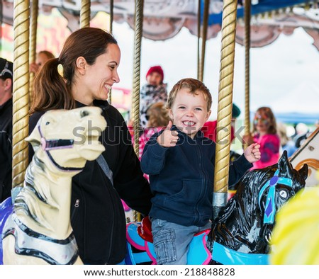A happy mother and son are riding on a merry-go-round carousel together, smiling and having fun at a fair or amusement park.  The boy holds a thumbs up.  - stock photo