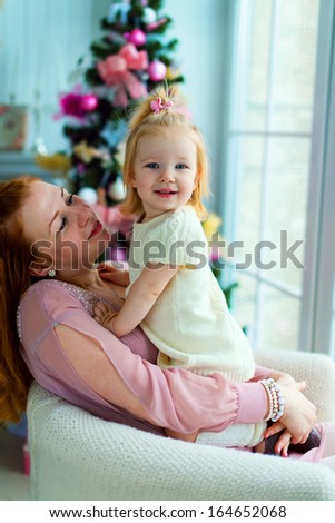 A happy mother holding her little daughter in her arms sitting on the armchair against the Christmas Tree - stock photo