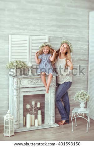 A happy mother is standing near her young daughter, who is sitting on the fireplace. They are laughing and having floral wreathes on. A girl and her mother are wearing casual clothes. - stock photo