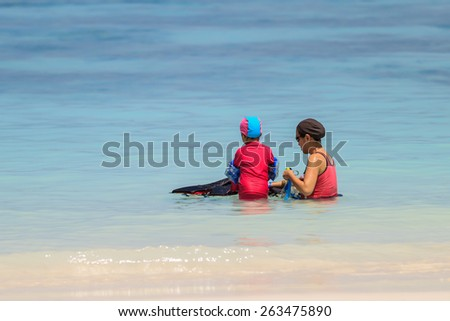 A happy mother with her child with snorkeling equipment on tropical beach - stock photo