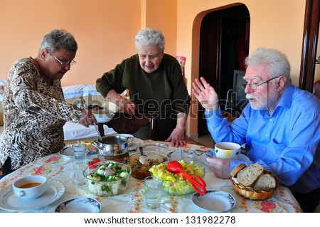 a happy old family having dinner together - stock photo