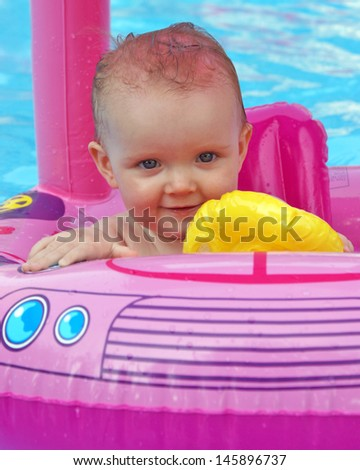 A happy one year old girl enjoys her summertime in the pool.
