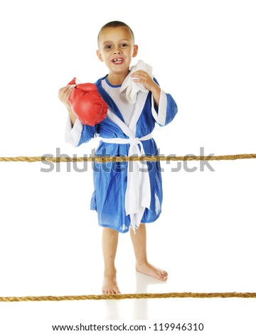 A happy preschool boxer behind ropes wearing his robe while holding his gloves and towel.  He has a tooth missing and a black eye. - stock photo