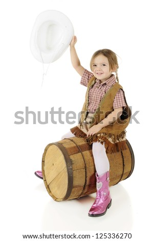 "A happy preschool cowgirl waving her hat as she ""rides"" a rustic, wooden barrel.  On a white background. - stock photo"