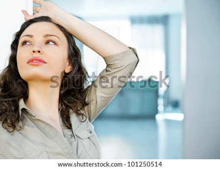 A happy relaxed young woman standing at entrance door of her home and relaxing - stock photo