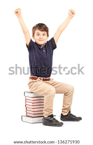 A happy school boy raised his hands gesturing happiness, seated on a pile of books against white background - stock photo