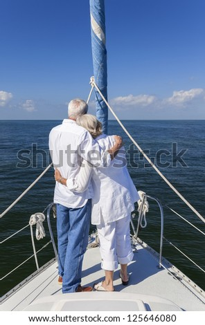 A happy senior couple embracing at the front or bow of a sail boat on a calm blue sea looking to a clear horizon - stock photo