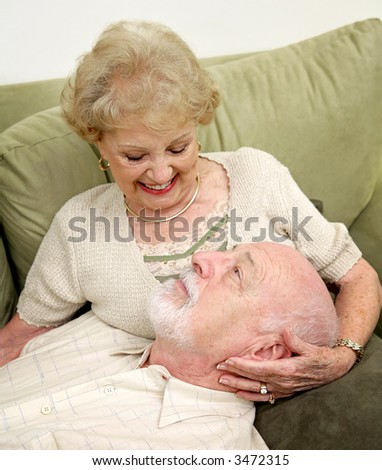 A happy senior couple relaxing together at home.  Focus is on him looking up at her. - stock photo