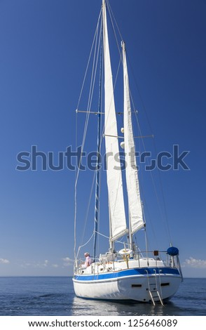 A happy senior couple sitting at the front or bow of a sail boat on a calm blue sea looking to a clear horizon