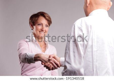 a happy senior woman handshaking - stock photo