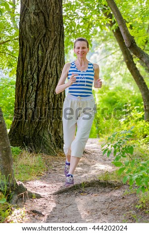 A happy senior woman is running in the forest close to the lake during a warm summer day - stock photo