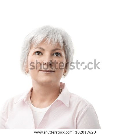 A happy senior woman looking up and thinking or contemplating. Isolated on a white background with copy space. - stock photo