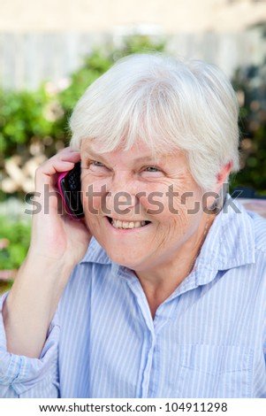 A happy senior woman smiles as she talks on her smartphone.