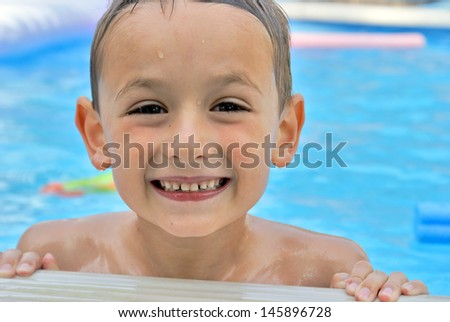 A happy six year old boy enjoys his summertime in the pool. - stock photo