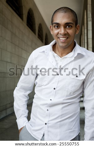 A happy, smiling, dark skin Asian young man looking at camera. - stock photo
