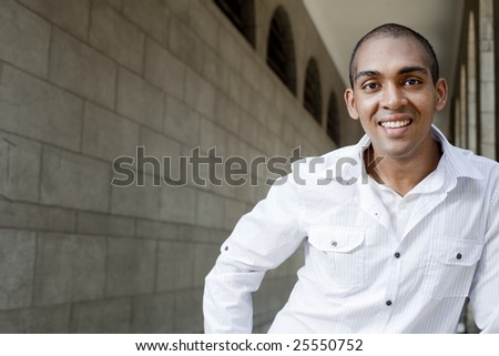 A happy, smiling, dark skin Asian young man looking at camera with space for copy on left - stock photo