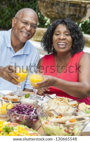 A happy, smiling man and woman senior African American couple eating healthy food at a picnic table outside - stock photo
