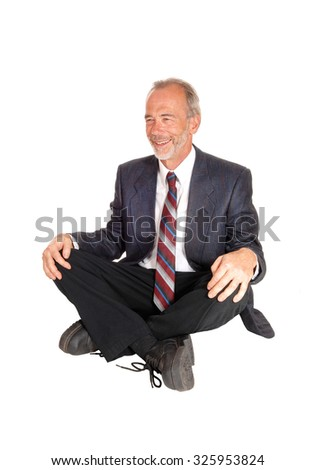 A happy smiling middle age businessman in a suit, sitting on the floor