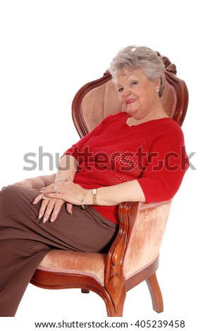 A happy smiling senior woman sitting in a pink armchair, relaxing,isolated for white background. - stock photo