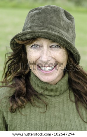 A happy smiling woman in her forties wearing a green hat and jumper. - stock photo